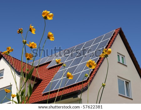 Solar cells on a roof with flowers in the foreground. - stock photo