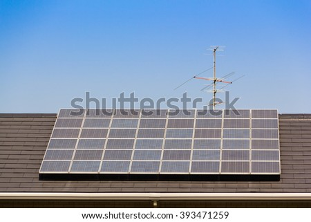solar cells on top of roof with metal Antenna against blue sky with text. concept : clean energy, selective energy    - stock photo
