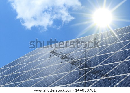 Solar cells with radiation ot the sun and power pole - stock photo