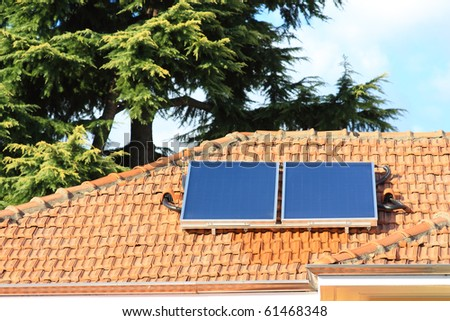 Solar collectors, used for hot water production, on a big roof - stock photo