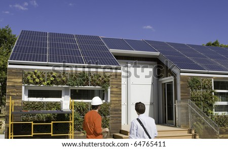 Solar construction workers looking at the roof.  Plants are from a gray water recovery system. - stock photo