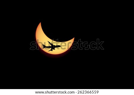 solar Eclipse and flying against the plane. - stock photo