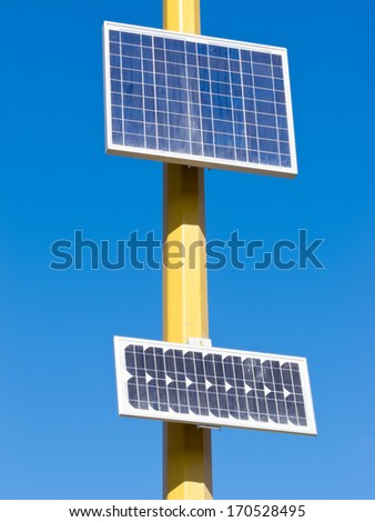 Solar electric panels mounted on yellow pole providing off-grid power in full sun against blue sky - stock photo