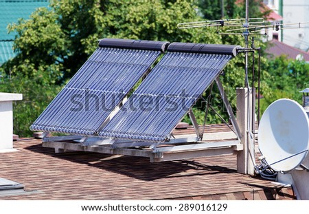 Solar energy collectors for heating the house stands on the roof - stock photo