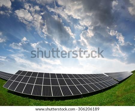 Solar energy panels against sunset sky - stock photo