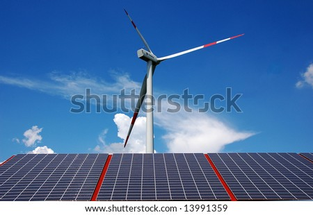 Solar energy panels and a windmill with blue sky and clouds