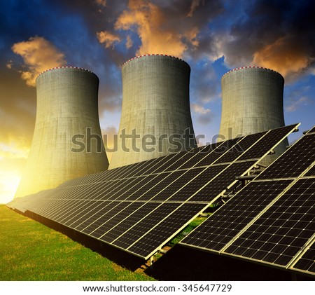 Solar energy panels and nuclear power plant at sunset. - stock photo