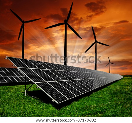 Solar energy panels and wind turbine in the setting sun