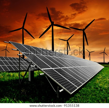 Solar energy panels and wind turbine in the setting sun - stock photo