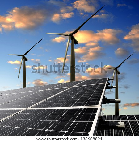 solar energy panels and wind turbine in the sunset - stock photo