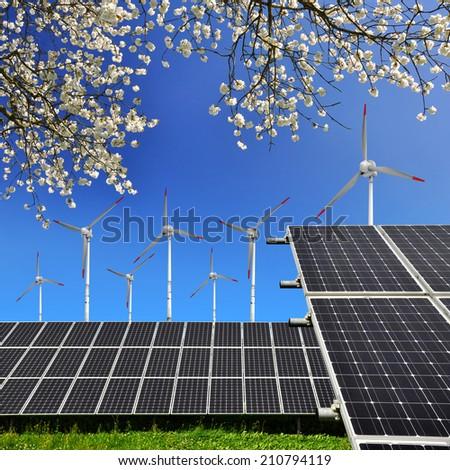 Solar energy panels and wind turbines against blue sky  - stock photo