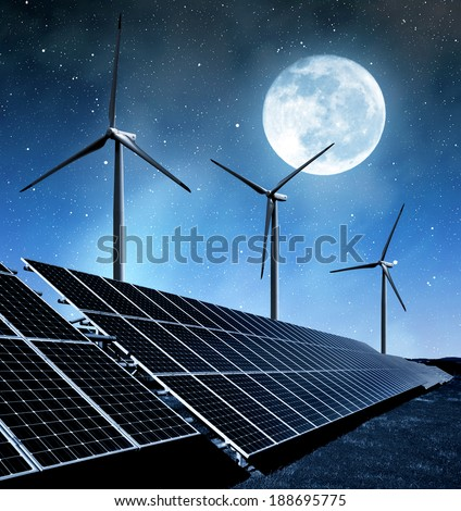 solar energy panels and wind turbines in night - stock photo