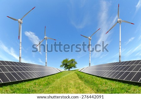 Solar energy panels and wind turbines on meadow. Alternative energy. - stock photo
