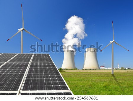 Solar energy panels before a nuclear power plant and wind turbines - stock photo