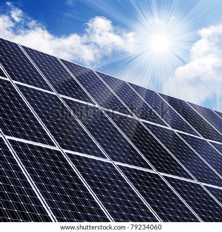 Solar energy panels in grass against sunny sky. - stock photo