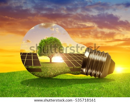 Solar energy panels in light bulb at sunset. The concept of sustainable resources.