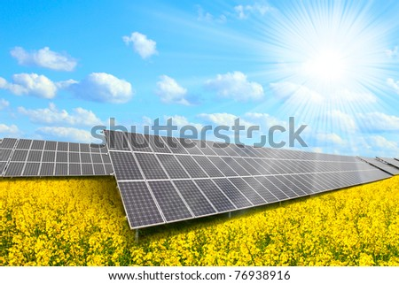 Solar energy panels on a rapeseed field against sunny sky.