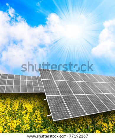 Solar energy panels on a rapeseed field against sunny sky. - stock photo