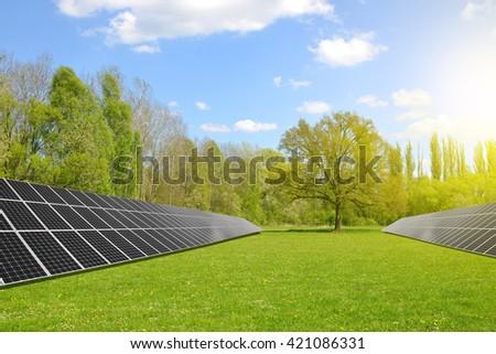 Solar energy panels on meadow. Clean energy. - stock photo