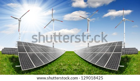 Solar energy panels with wind turbines against blue sky with clouds