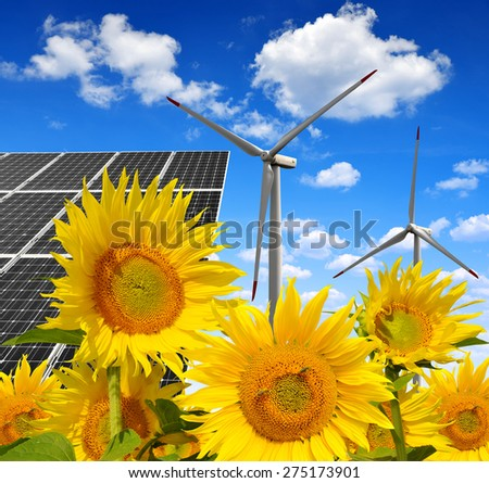 Solar energy panels with wind turbines in sunflower field. Green energy. - stock photo