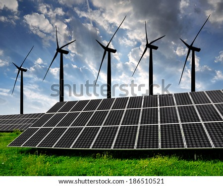 Solar energy panels with wind turbines in the setting sun