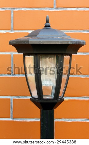 solar garden lamp on background of wall - stock photo