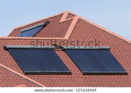 Solar glass tube hot water panel array mounted on a tiled roof