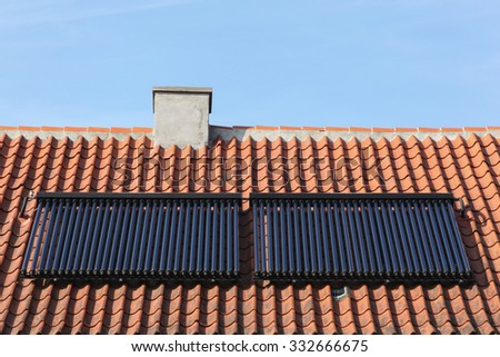 Solar glass tube hot water panel array on a roof  - stock photo