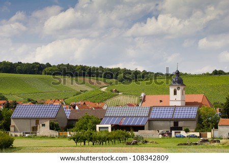 Solar mirrors installed on the roofs of a small village with church and farmhouses in Franconia, Bavaria (Germany). - stock photo