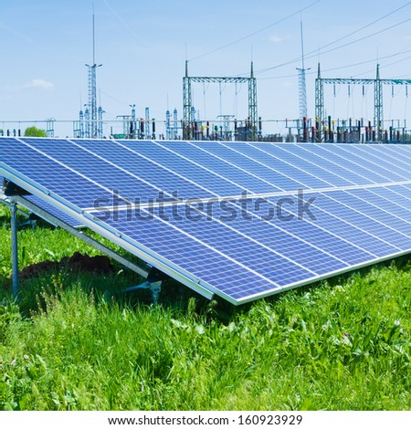 solar panel against high voltage towers - stock photo