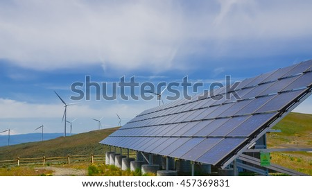 Solar panel and row of wind turbines under cloud blue sky at Ellensburg, Washington, US. Power plant generates renewable energy from sun and wind. Clean, sustainable power concept. Panorama style.