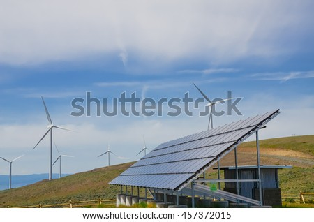 Solar panel and row of wind turbines under cloud blue sky at Ellensburg, Washington, US. Power plant generates renewable energy from sun and wind. Clean, sustainable power concept. Green energy source - stock photo