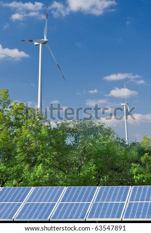 Solar panel and wind mill in front of blue sky - alternative energy sources concept - stock photo