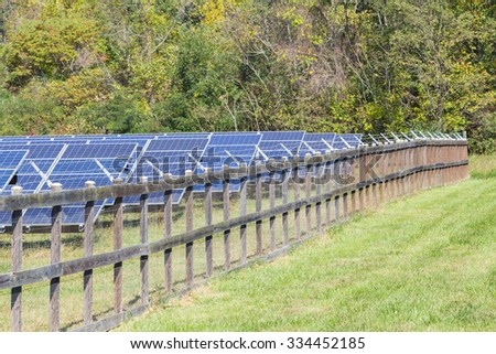 Solar panel array protected by sturdy wood and wire fencing under the intense sun in North Carolina. - stock photo