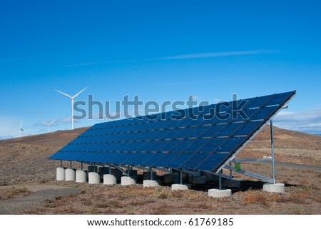 Solar panel array with wind turbines in background - stock photo