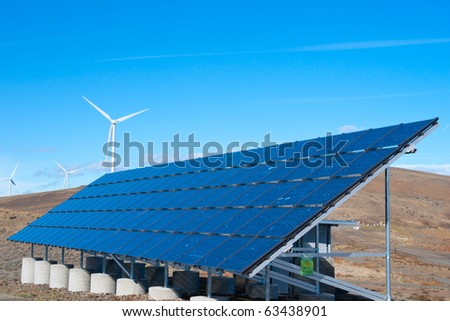 Solar panel array with wind turbines in background