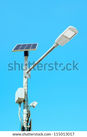 Solar panel cell powered street light lamp on a blue sky background