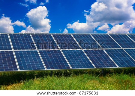 Solar panel in a field under a blue sky