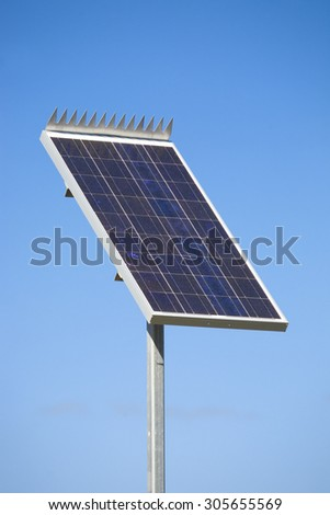 Solar panel in a remote village against clear blue sky