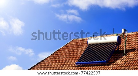 Solar panel on a domestic house, with clear blue sky, lots of clouds and a sun - stock photo