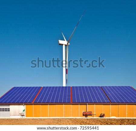 Solar panel on a farm building with a wind mill in the background - stock photo