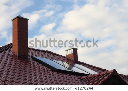 Solar panel on a roof cloudy sky - stock photo