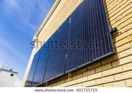 Solar panel on orange wall reflecting the sun and blue sky - stock photo