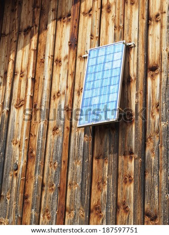 Solar panel on the wooden wall of a barn - stock photo