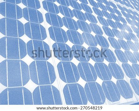 Solar panel photovoltaic cells array close up  illustration with cumulus clouds reflected in the panels. Solar energy, an ecofriendly power source, uses the sun to generate clean renewable energy. - stock photo