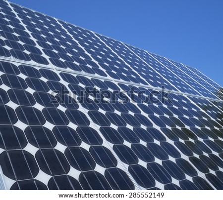 Solar panel photovoltaic cells array close up with blue sky copy space. Solar energy is an ecofriendly power source which uses the sun to generate clean renewable energy. - stock photo