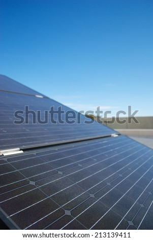 Solar panel (Photovoltaic panels) on an industrial roof. Blue sky on the background.