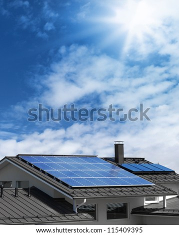 Solar panel system on house roof, sunny blue sky background - stock photo