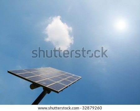 Solar panel under blue sky with sun flare - stock photo